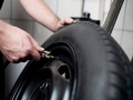 Mechanic deflating vehicle tyre closeup
